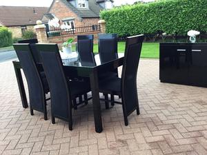 Black high shine dining room table and six chairs. Matching side cabinet