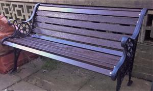 Two seater recently refurbished outdoor bench with wrought iron ornate ends.