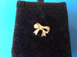 Small gold plated bow pin with clear stones