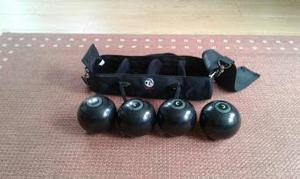A set of rink bowls in a carrying bag with shoulder strap.