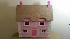 Large pink doll's house with furniture and people