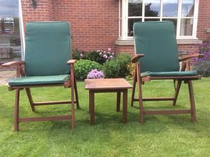 Set of two garden chairs with cushions and small table.