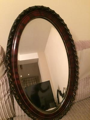 Vintage heavy oval mirror with carved mahogany frame