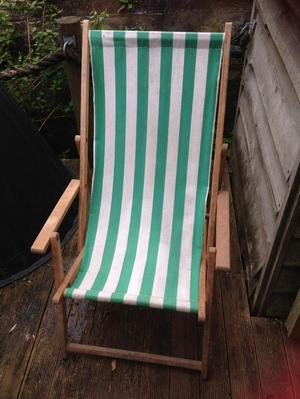 2 green and white striped fabric deckchairs