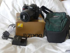 Nikon D digital camera together with charger, nikon lens DX and camera case.