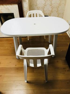 Plastic table with two white chairs