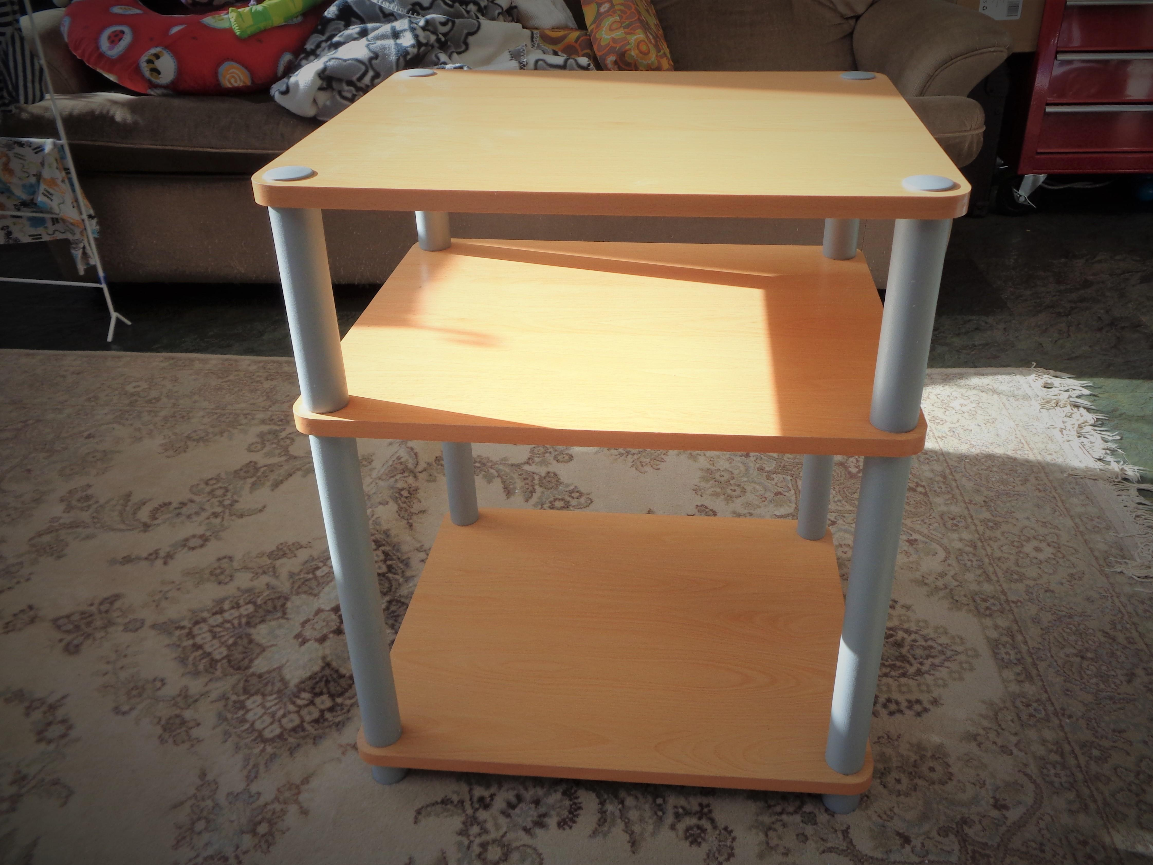 Small table with plastic towers and 3 wooden shelves.
