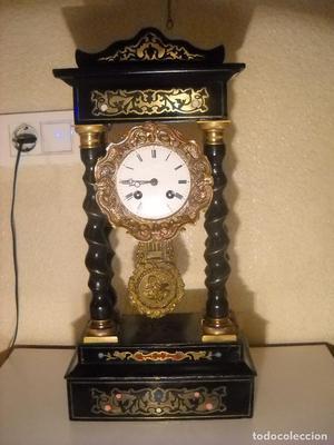 Antiguo reloj de pórtico con marquetería metálica e