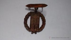 Medalla de latón con laureles, libro y la cruz