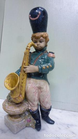Figura de cerámica, porcelana. Niño soldado con saxo. PAL