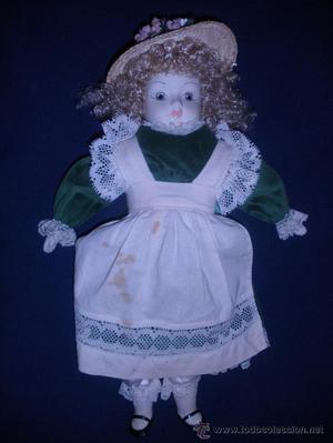 Antigua muñeca con cabeza y extremidades de porcelana.
