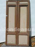 Doble puerta antigua con cristales y contaventanas para