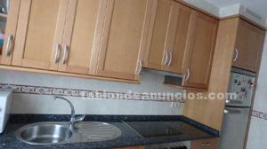 Muebles de cocina con electrodomésticos y mesa