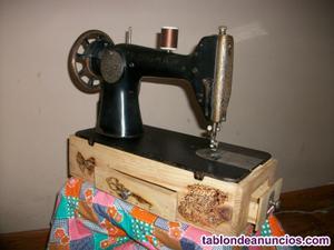 Máquina de coser sigma sobre caja decorada con cajones.