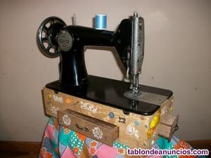 Maquina de coser sigma sobre caja decorada con cajones.