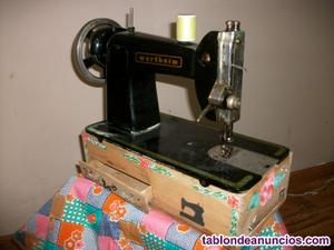 Maquina de coser wertheim sobre caja decorada con cajones.