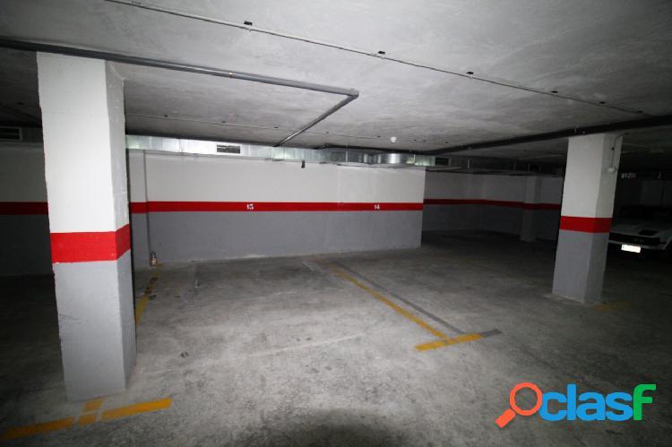 Amplia plaza de garaje con montacoches en el centro de